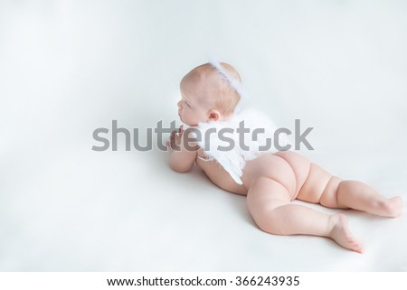 Soft image of cute newborn baby lying on white background covered with white angel's wings and halo nimbus made of feathers