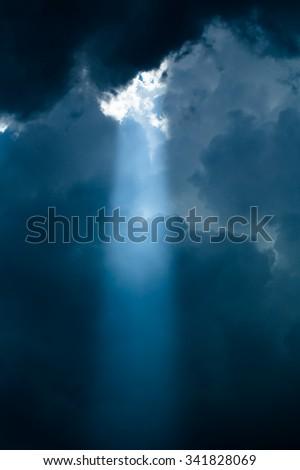 soft light Rays of light shining down ground. dark sky with sun rays - stock photo