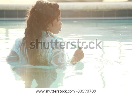Soft over-exposed view of a sexy Caribbean girl at the pool - stock photo