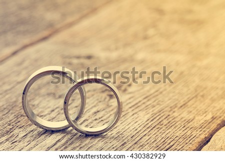 Soft pastel image with wedding rings on wooden background - stock photo