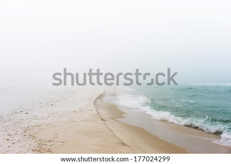Soft pastel landscape photo of waves breaking on a pristine, peaceful, unpopulated beach. - stock photo