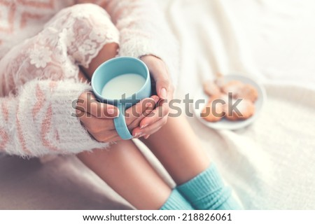 Soft photo of woman on the bed with cup of milk in hands, top view point - stock photo