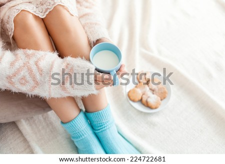 Soft photo of woman on the bed with cup of milk in hands, top view point. Cozy, comfy, soft - stock photo
