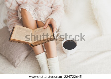 Soft photo of woman on the bed with old book and cup of coffee, top view point - stock photo