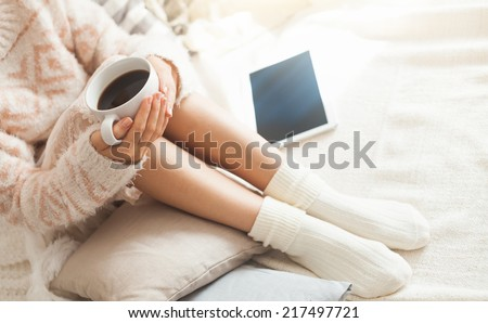 Soft photo of woman on the bed with tablet and cup of coffee in hands, top view point - stock photo