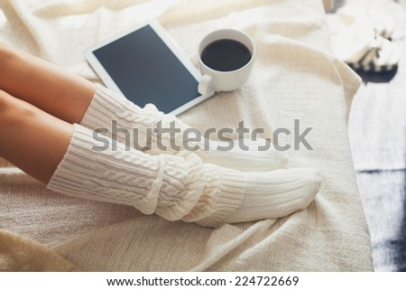 Soft photo of woman on the bed with tablet and cup of coffee, top view point - stock photo