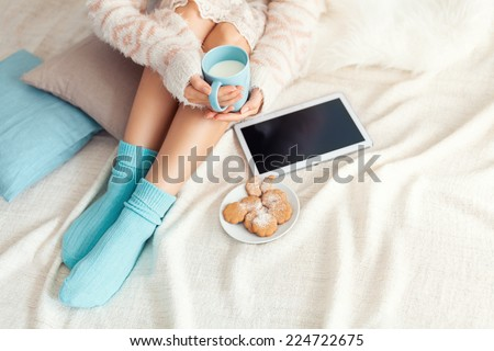 Soft photo of woman on the bed with tablet and cup of milk in hands, top view point. Cozy, comfy, soft - stock photo