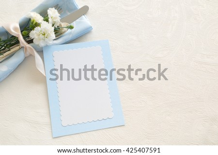 Soft Place setting with Silverware, pastel blue napkin, vertical blank name card and carnations on side on cream tablecloth with room or space for copy, text, your words. Horizontal with aerial view