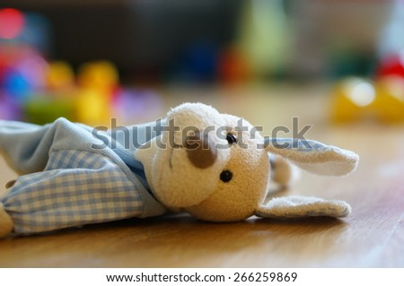 Soft plush dog lying on the floor - stock photo