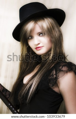 Soft portrait of a beautiful vintage girl in top hat and lace leotard performing on in front of stage curtains in a broadway dancer conceptual - stock photo