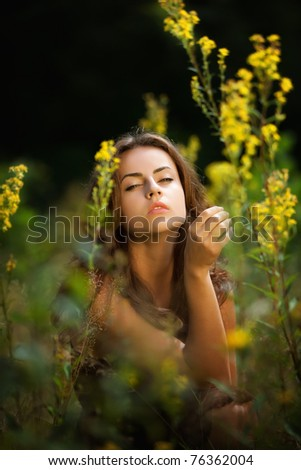 Soft portrait of a young woman on flowers field blured background - stock photo