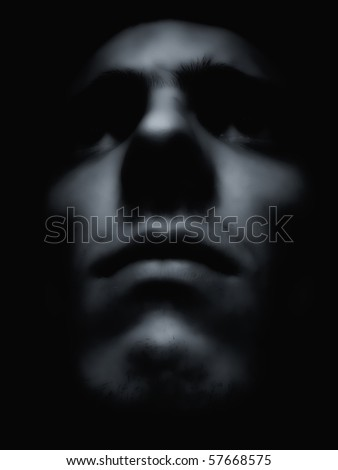 Soft portrait of an expressive man merging from the dark - stock photo