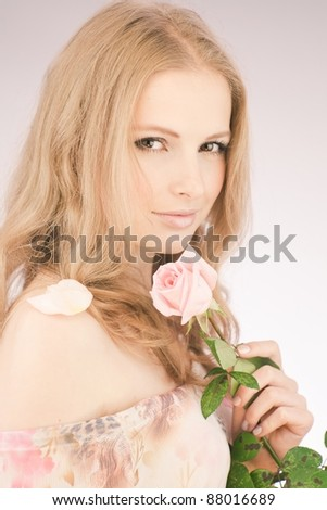 Soft portrait of beautiful girl with a pink rose - stock photo