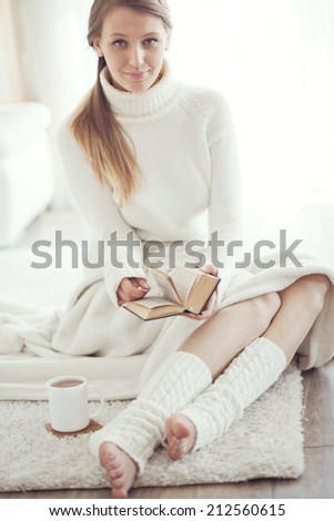 Soft portrait of teenage girl reading book at home - stock photo