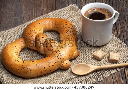 Soft pretzels with cup of hot coffee for breakfast on a rough fabric located on the table
