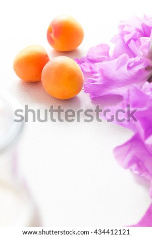 Soft ripe apricots and the light purple flowers on a white background.