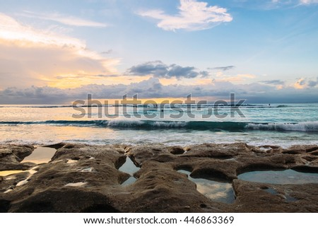 Soft sunset at fantastic sea beach made of rocks with holes filled by seawater in Bali. Sunset on a beach. Light sunset in Bali. Amazing sunset in Bali. Exotic sunset clouds of Bali. Sunset sea, Bali. - stock photo