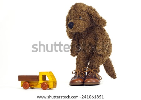 Soft toy dog looking at toy - stock photo