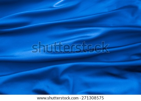 Soft velvet piece of blue fabric with folds to be used as background - stock photo