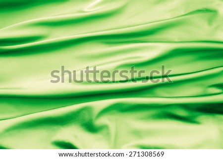 Soft velvet piece of green fabric with folds to be used as background - stock photo