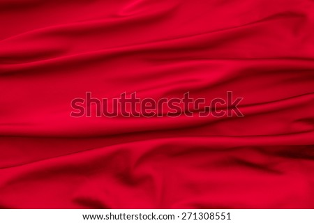 Soft velvet piece of red fabric with folds to be used as background - stock photo