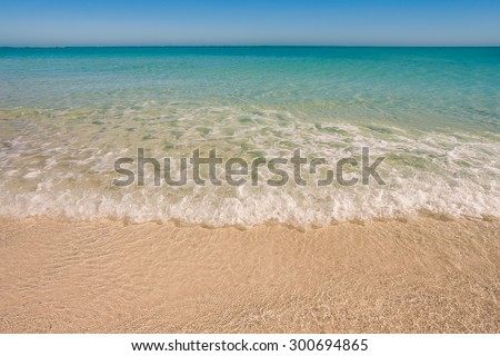 Soft wave of the lagoon on the sandy beach - stock photo