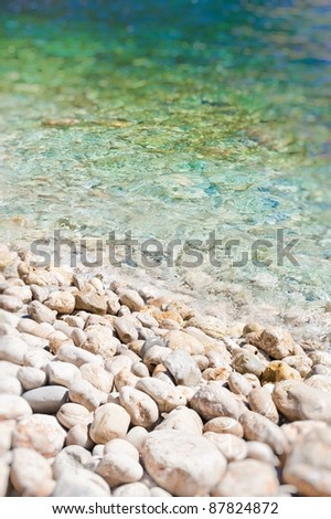 Soft wave of the sea on the pebble-stone beach - stock photo
