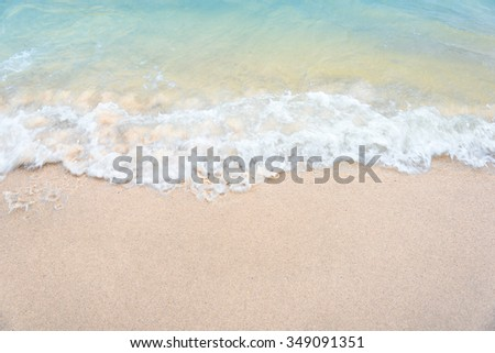 Soft wave of the sea on the sandy beach before the sunset - Motion blurred. - stock photo