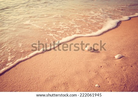 Soft wave of the sea on the sandy beach. Vintage filter. - stock photo