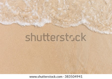Soft wave of the sea on the sandy beach with white clean foam. Copy space - stock photo
