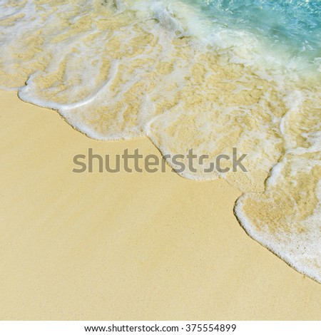 Soft wave of the tropical sea on the sandy beach - stock photo