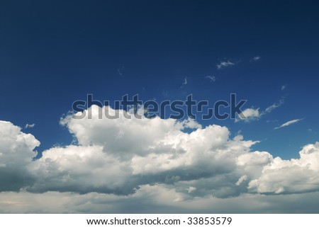 Soft white clouds against dark blue sky - stock photo