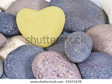 Soft yellow heart shaped stone on multi-colored stones - can be used for Valentine's day - stock photo