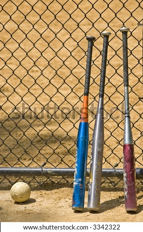 Softball and three bats leaning against a fence at a ball field in Central Park in New York City. - stock photo