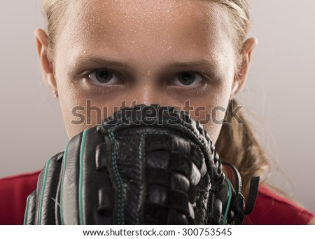 Softball girl with sweat looking from behind a mitt - stock photo