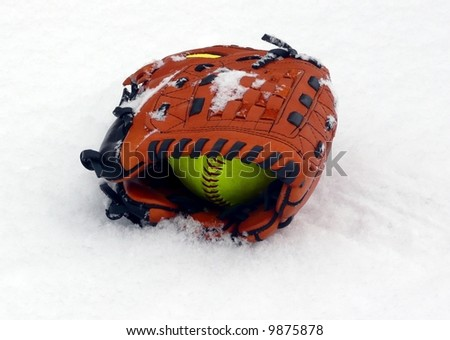 Softball glove and ball left outside in the winter snow - stock photo
