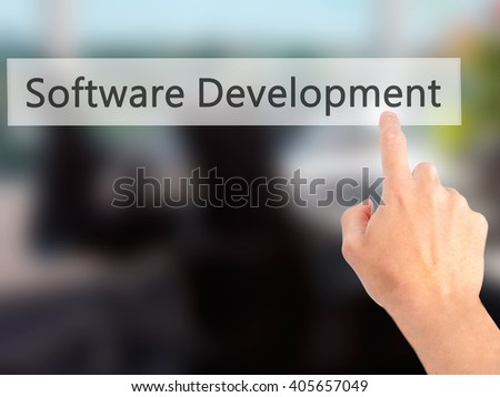 Software Development - Hand pressing a button on blurred background concept . Business, technology, internet concept. Stock Photo - stock photo