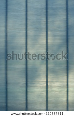 Softy frosted opaque glass with with diffuse lines and shadows playing across the surface. Greenish blue colors