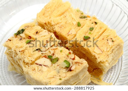 Sohan Papdi - an indian sweet beautifully place in a glass bowl isolated on white