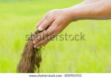 Soil, Agriculture, Compost ,Slow motion, Farmer hands holding and pouring organic fertilizer on green background - stock photo