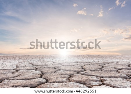 Soil drought cracked landscape on sunset sky background - stock photo