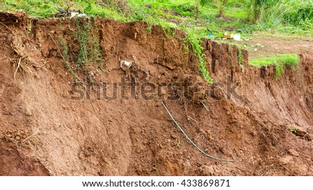 Soil slides down the river bank erosion due to water damage which has underground grass grow. - stock photo