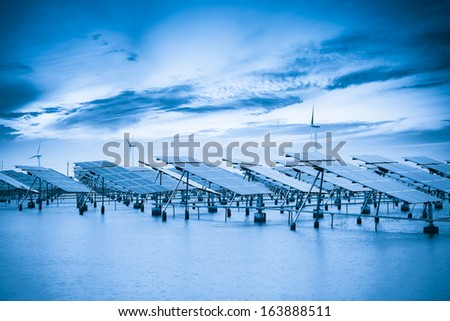 solar and wind power in coastal mud flat with blue tone - stock photo