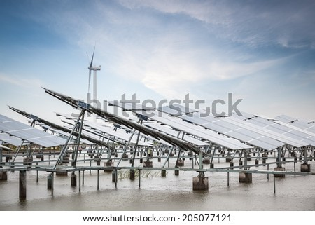 solar and wind power in coastal tidal flats ,green energy concept  - stock photo