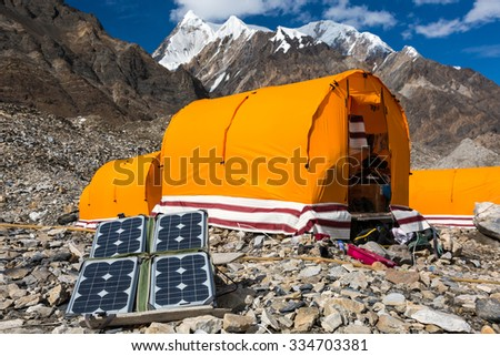 Solar Battery on Rocky Glacier Moraine for Electricity Supply of Sport Mountain Expedition in Wilderness Country with Camping Tents on Background - stock photo