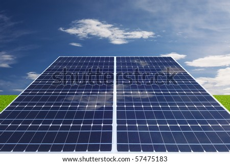 solar cell on grass field with nice cloudy sky in back - stock photo