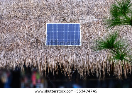 Solar cell on thatched roof for energy in forest. - stock photo