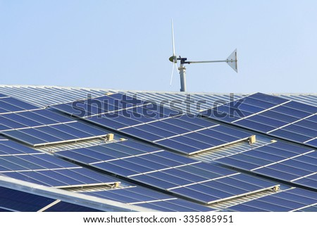 solar cell panel and wind turbines on factory roof - stock photo