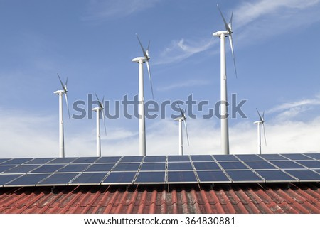 solar cell panel and wind turbines on red roof and cloud blue sky , Energy saving concept - stock photo