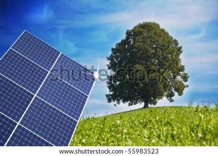 Solar cell with a symbolic tree in back - stock photo